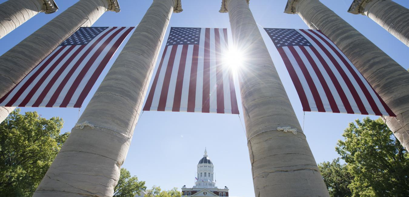 Image: Columns on the Francis Quadrangle adorned with American flags.