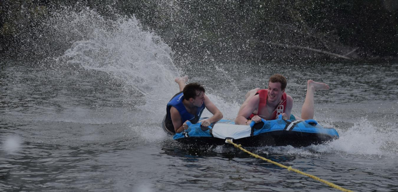 Image: Two camp Trulaske students on an inter tube being pulled on a lake.