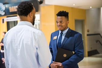 Image: Male student talking to a recruiter at a MU BCS career fair.