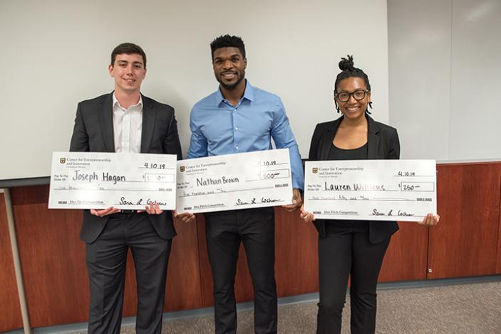 Image: CEI Venture pitch competition top 3 finishers, Joseph Hagan, Nathan Brown and Lauren Williams, holding big checks.