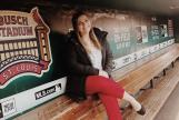 Image: Bailey Stamp sitting in the dugout at Busch Stadium in St. Louis.